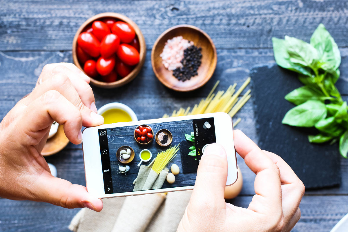 socil network marketing definition: man taking photo of food for Instagram